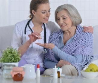nurse giving medicine to an elder woman