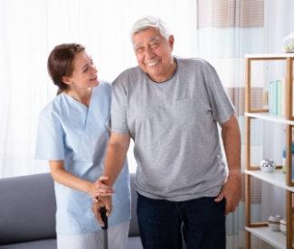Female Caretaker Assisting Happy Senior Man While Walking At Home