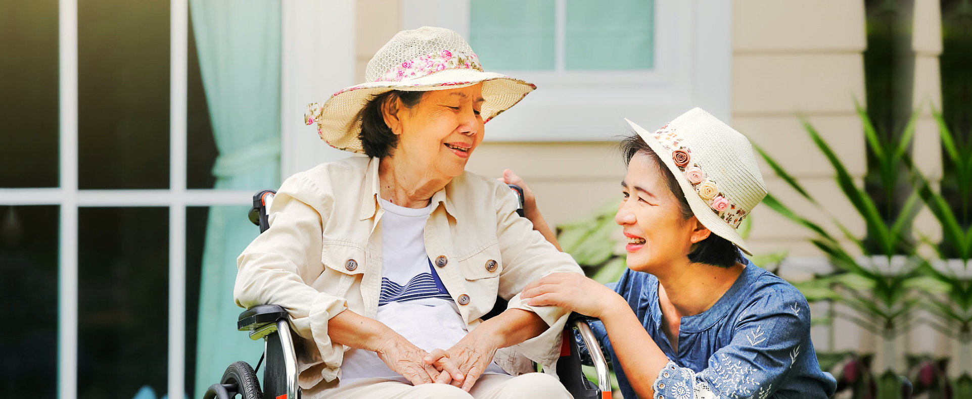 elder woman sitting on a wheelchair with caregiver beside her