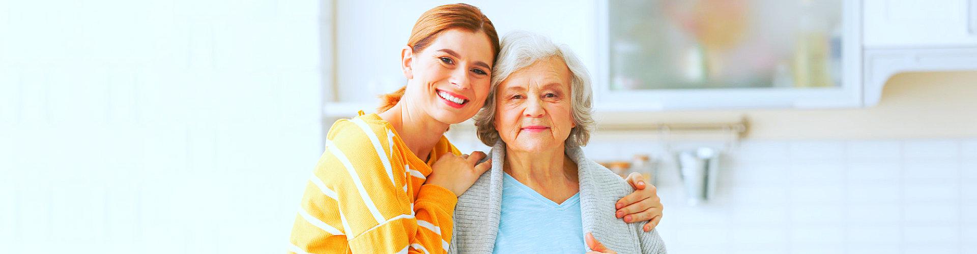 caregiver hugging elder woman