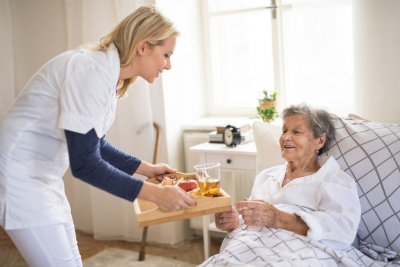 nurse giving senior a food